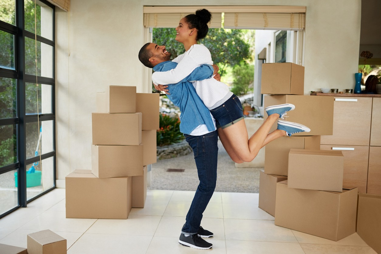 happy young couple celebrating their move in new home